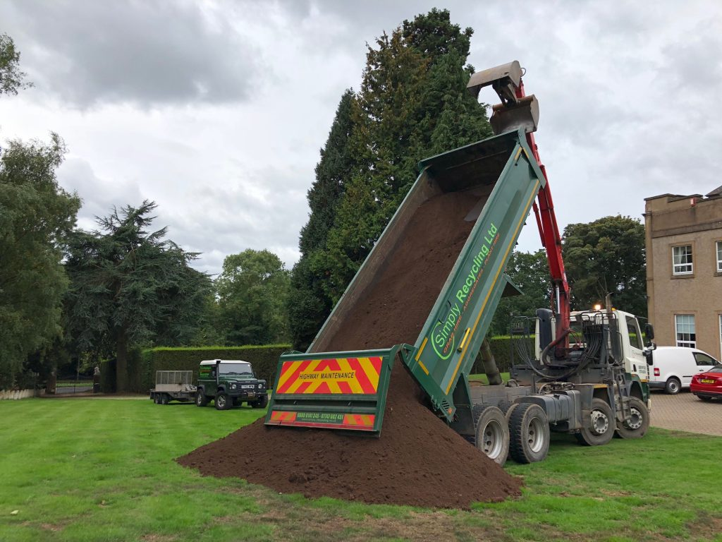 Grab lorry tipping off screened topsoil in Birmingham, West Midlands.